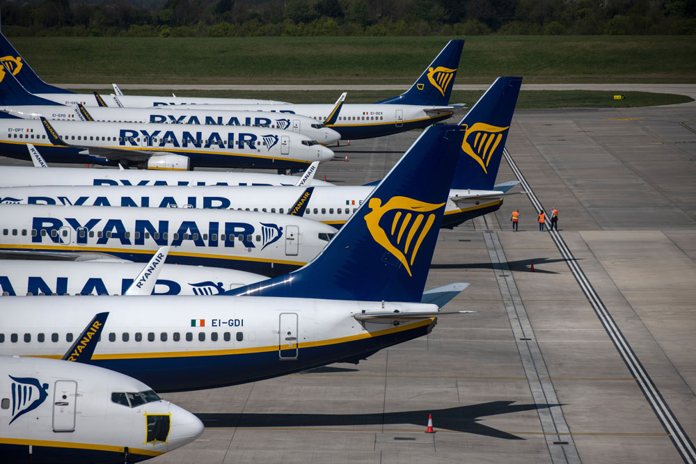 Three people walk on the runway near parked Ryanair passenger planes at Stansted Airport on April 15 in Essex.