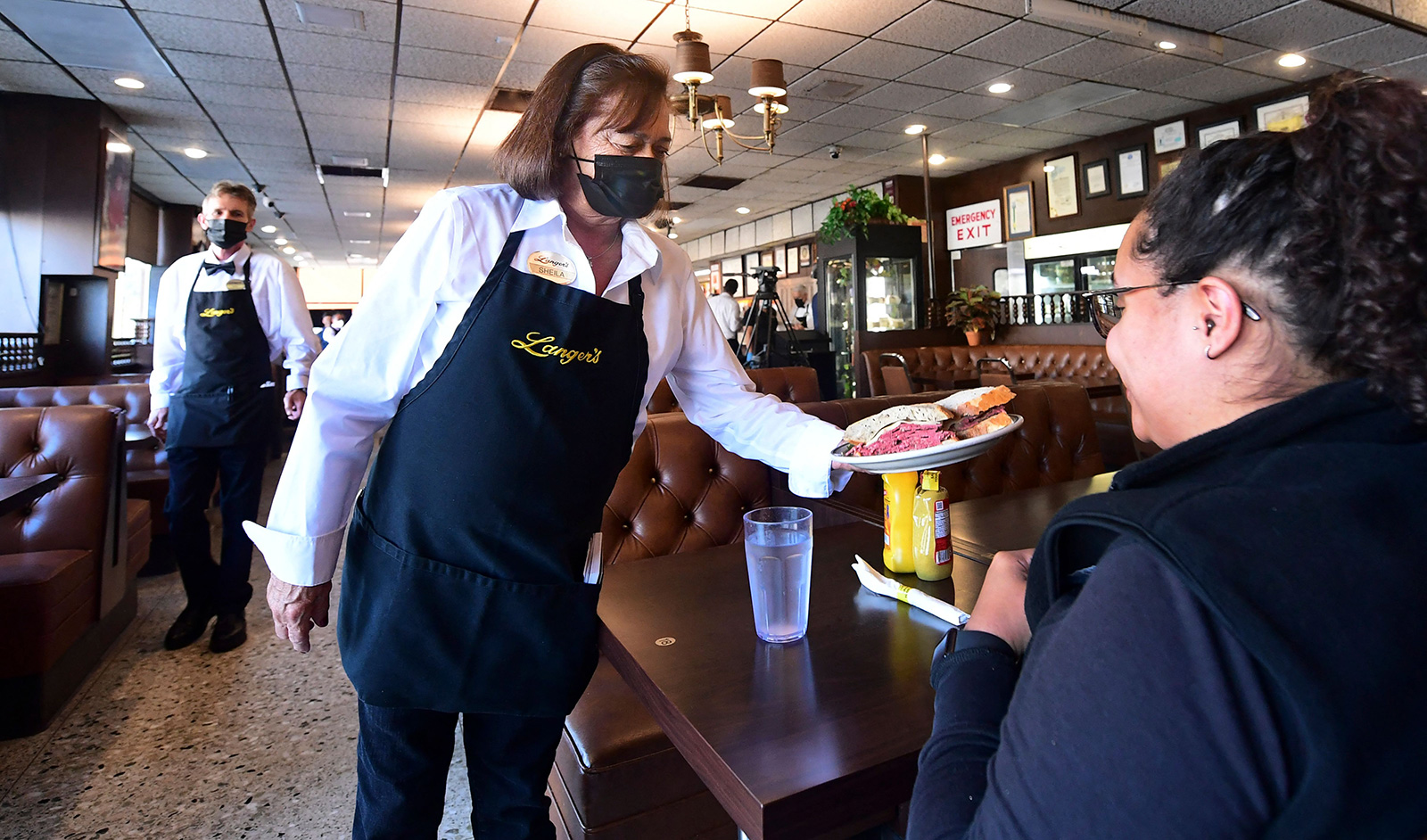 Waitress, and twenty-year employee, Sheila Abramson delivers a corned beef sandwich to a customer at the reopening of Langer's Delicatessen-Restaurant in Los Angeles on June 15, as California lifts its Covid-19 restrictions.