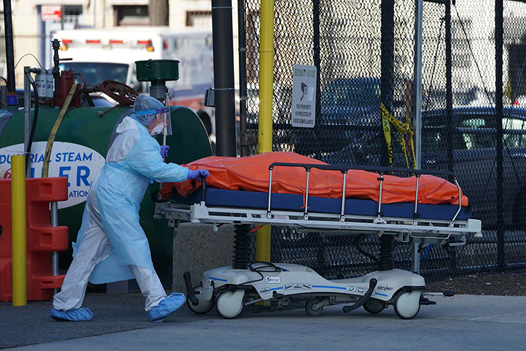 A body is moved to a refrigerator truck serving as a temporary morgue outside of Wyckoff Hospital in Brooklyn on April 4, in New York.
