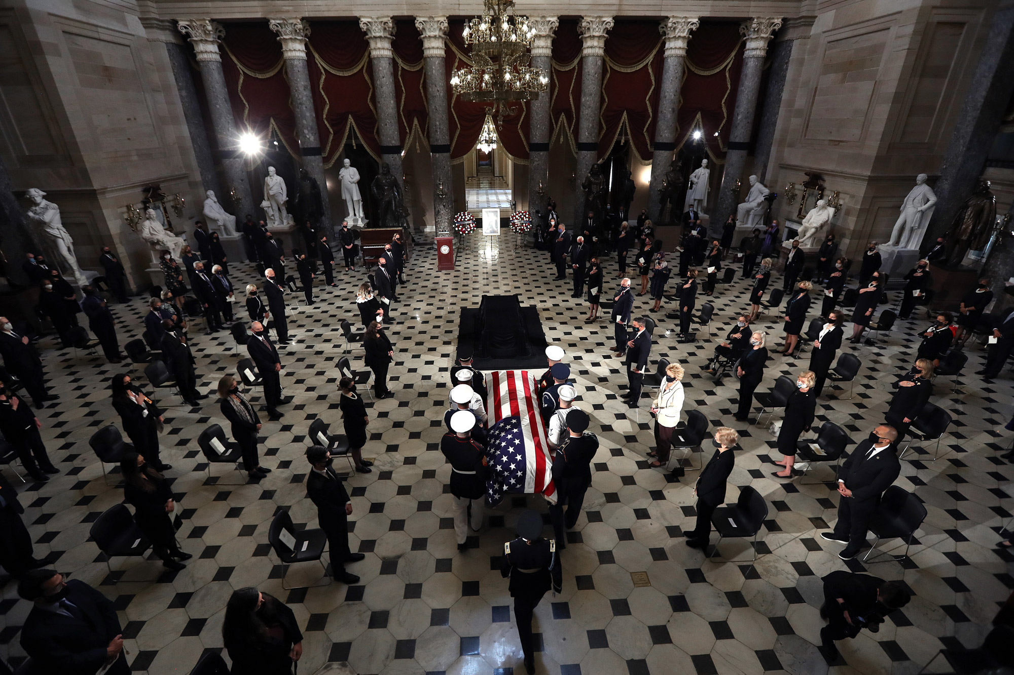 U.S. Supreme Court Associate Justice Ruth Bader Ginsburg's flag-draped casket is carried into Statuary Hall where she will lie in state at the U.S. Capitol on September 25 in Washington, DC.