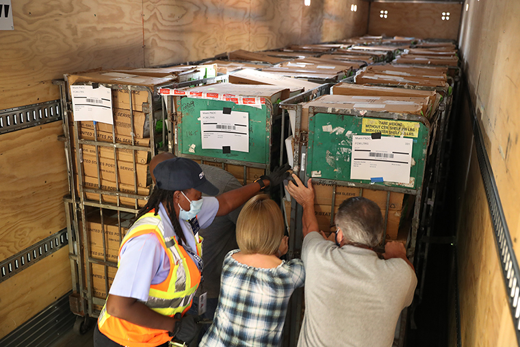 Workers at the Miami-Dade County Election Department move racks of vote-by-mail ballots onto a U.S. Post Office truck to be delivered to voters on October 01, in Doral, Florida.