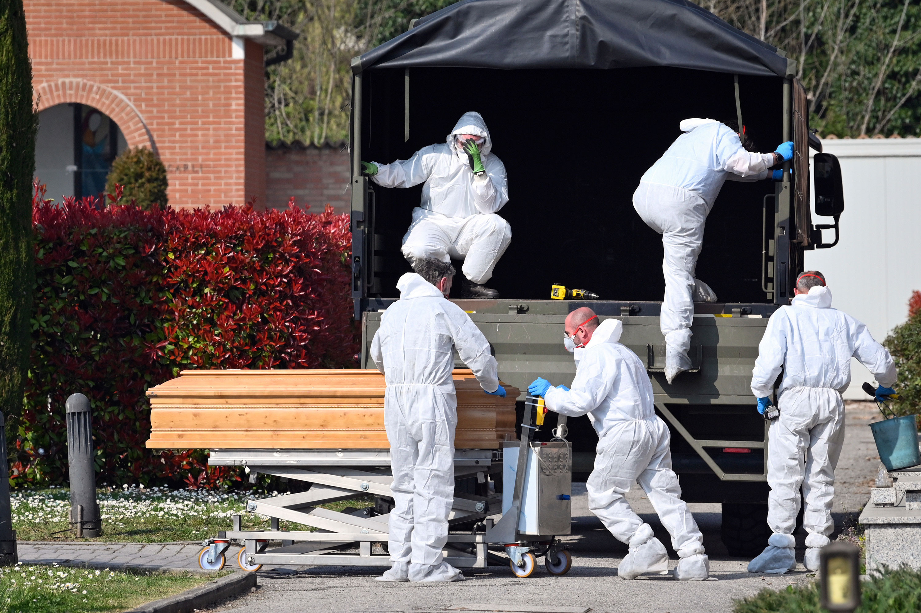 Coffins are downloaded at the Ferrara cemetery, from a military convoy coming from Bergamo, a city at the epicenter of the coronavirus outbreak in northern Italy, March 21.