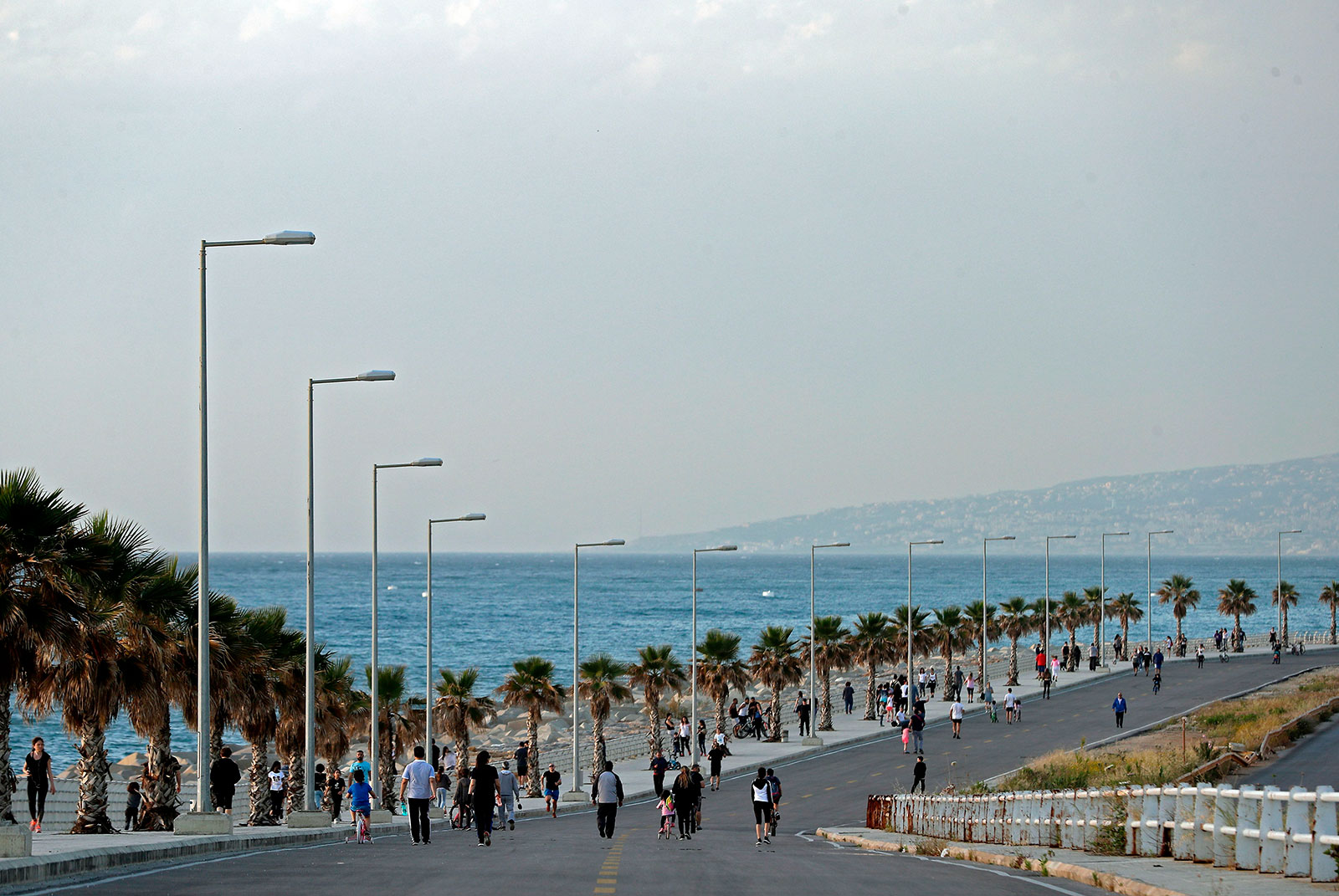 Lebanese people exercise on an empty road by the Dbayeh seaside promenade in Beirut on May 8.