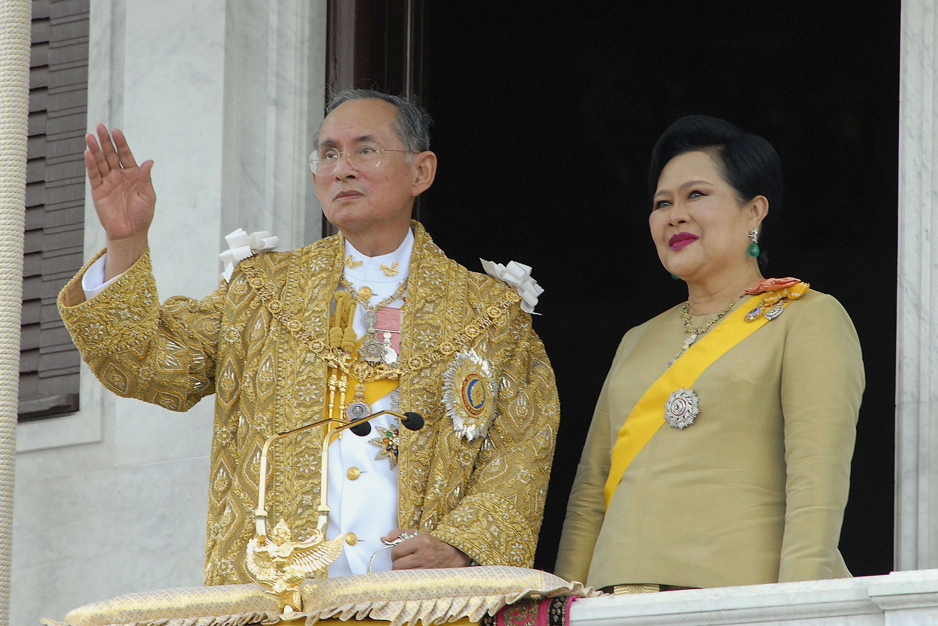 Thailand's King Bhumibol Adulyadej and Queen Sirikit wave to thousands of people waiting outside the Royal Plaza to pay tribute to him on June 9, 2006 in Bangkok, Thailand, as the country began a five-day celebration to mark the 60th anniversary of his accession to the throne.