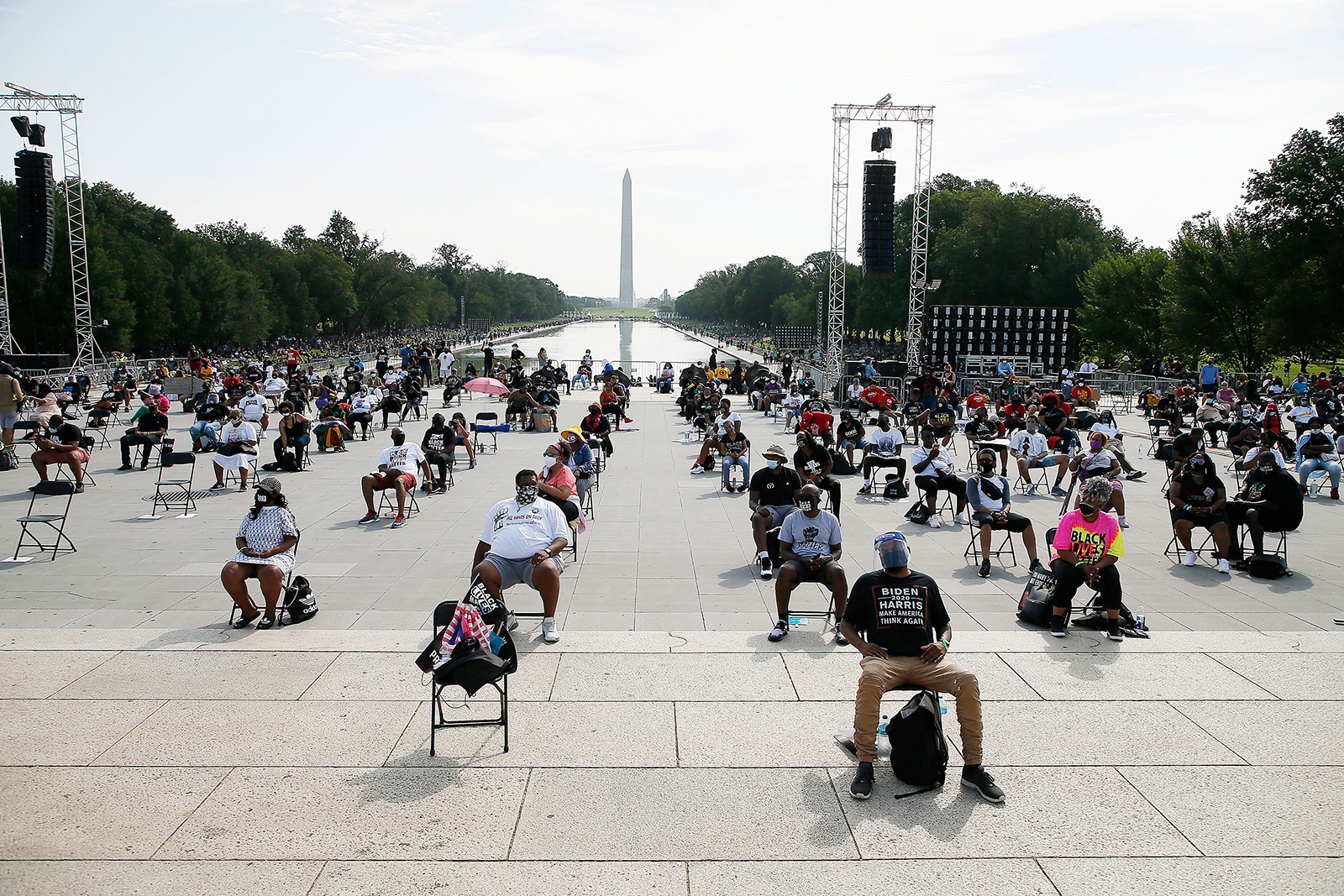 "Attendees sit socially distanced at the 2020 March on Washington, officially known as the ""Commitment March: Get Your Knee Off our Necks,"" at the Lincoln Memorial on Friday in Washington."