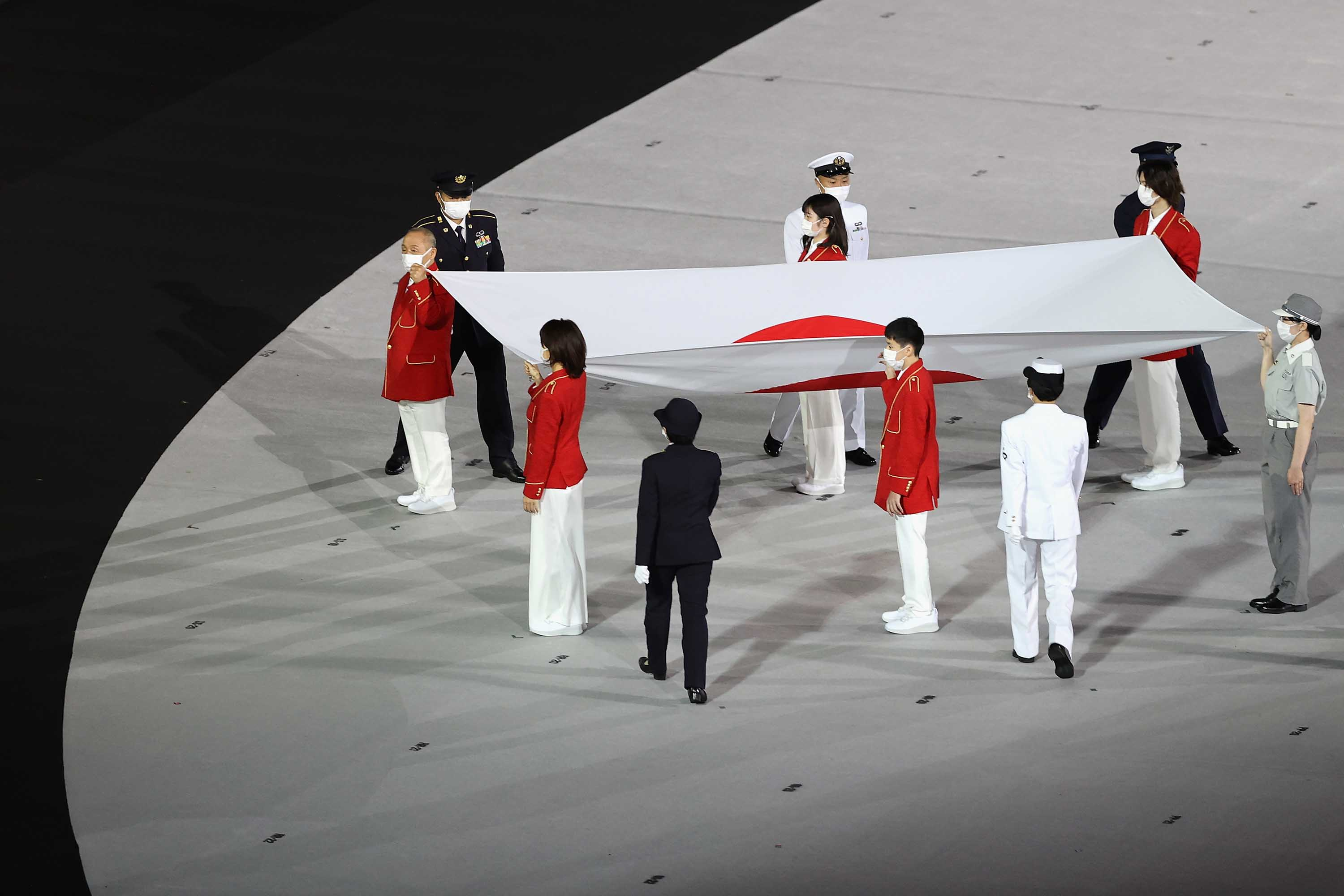 The Japanese flag is carried on stage during the Opening Ceremony.