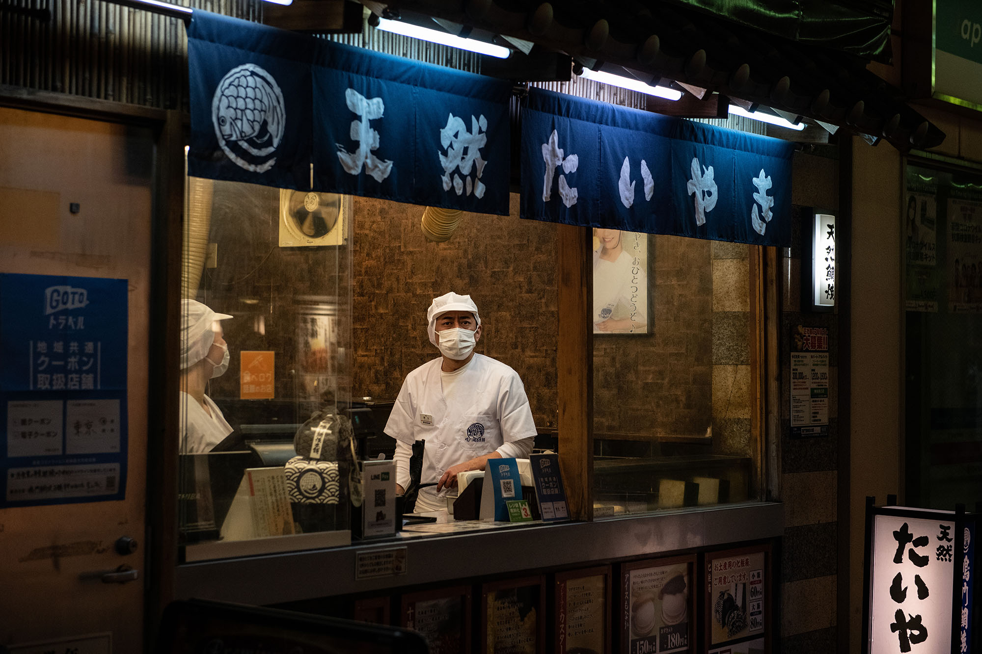 A chef wearing a face mask looks out from a restaurant window on December 23, in Tokyo, Japan.