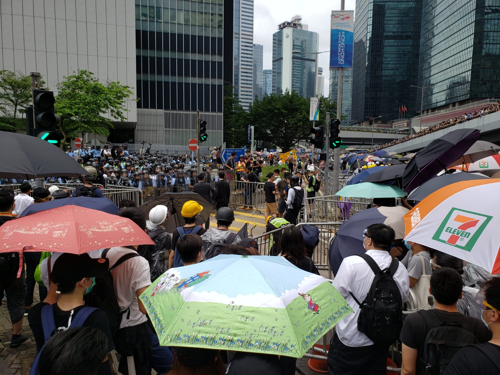 Protesters hand out anti-tear gear and masks by Tim Wa Avenue.