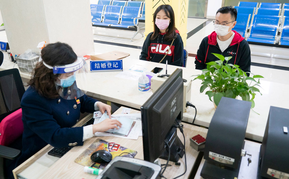 A couple go through marital procedures at a marriage register office in Wuhan, central China's Hubei Province, on April 7.