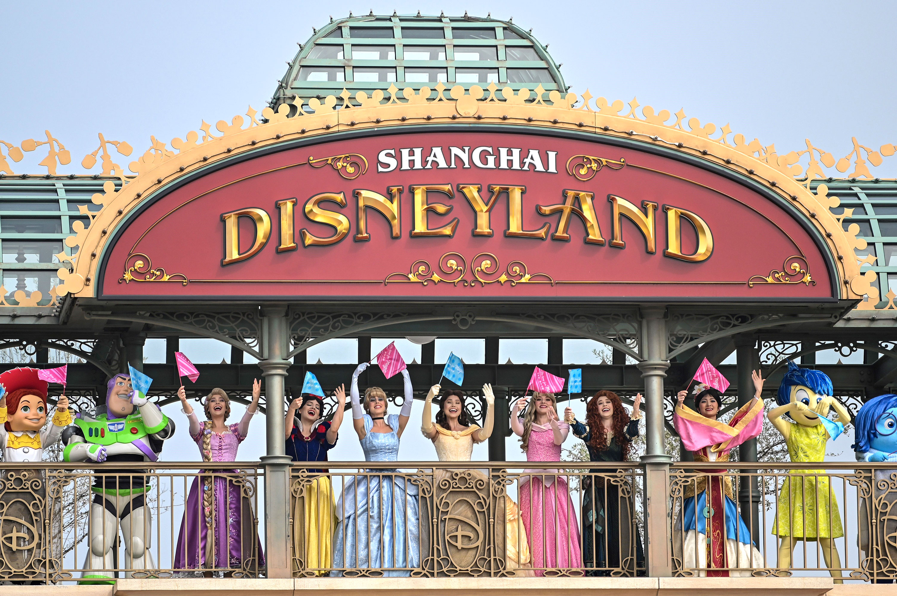 Performers dressed as Disney characters welcome visitors during the reopening of Disneyland Shanghai on May 11 in Shanghai, China.
