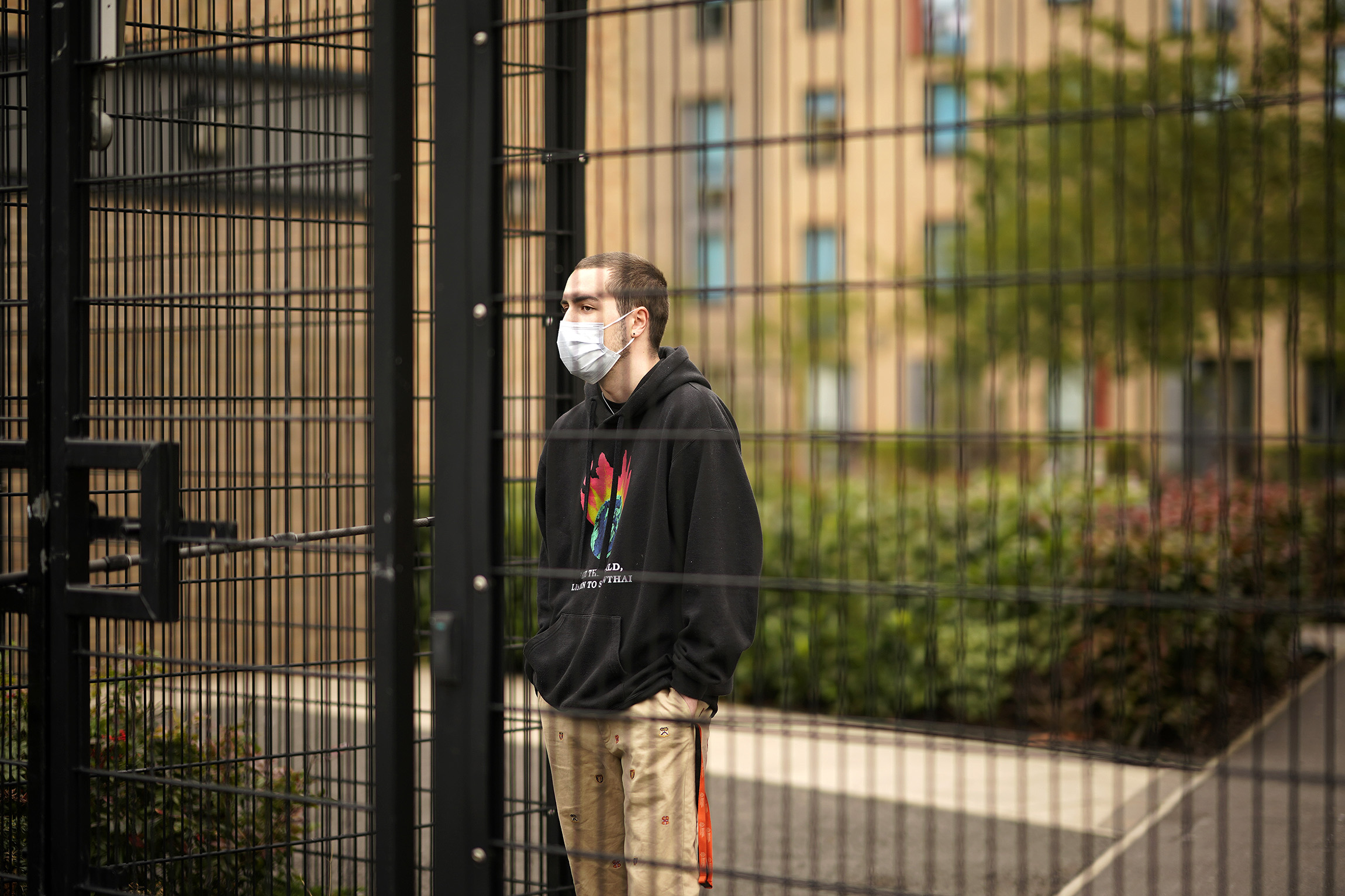 Students who are self-isolating stand behind security fencing as they are interviewed by a television crew on September 28, in Manchester, England.