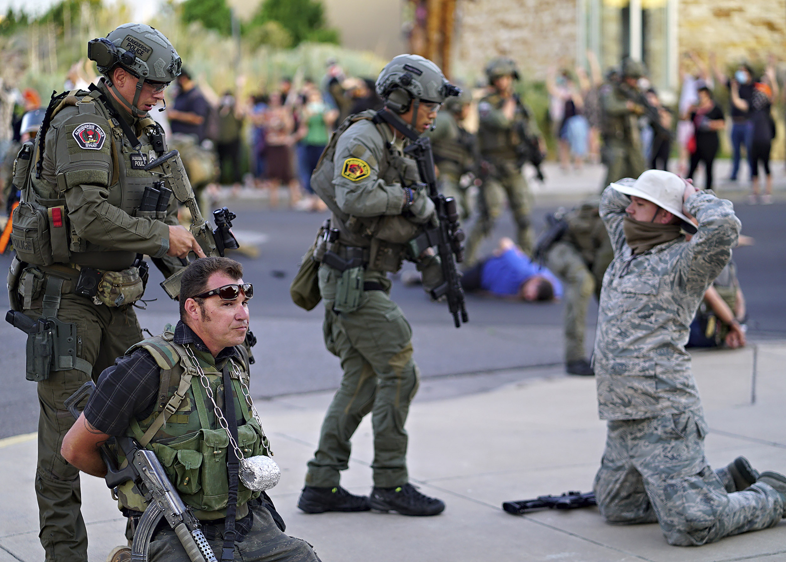 Albuquerque police detain members of the New Mexico Civil Guard, an armed civilian group, following the shooting of a man during a protest over a statue of Spanish conquerer Juan de Oñate on Monday, June 15, in Albuquerque, New Mexico.