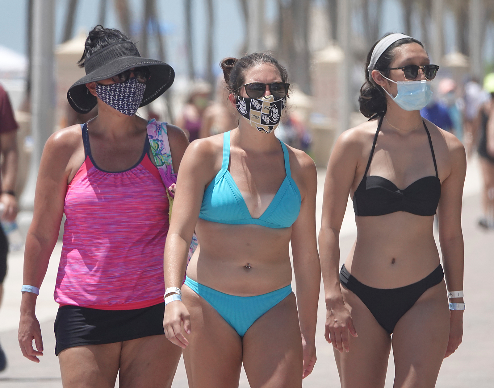 Beachgoers wear masks on the Hollywood Beach Broadwalk, on July 19 in Hollywood, Florida.