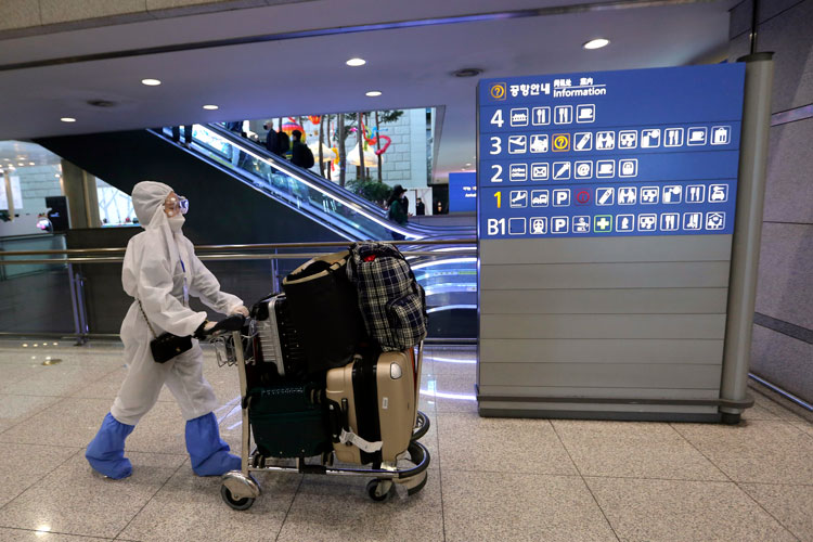 A woman wearing protective gear moves luggage as she waits for her flight at the Incheon Airport in Incheon, South Korea, on Thursday, March 19.