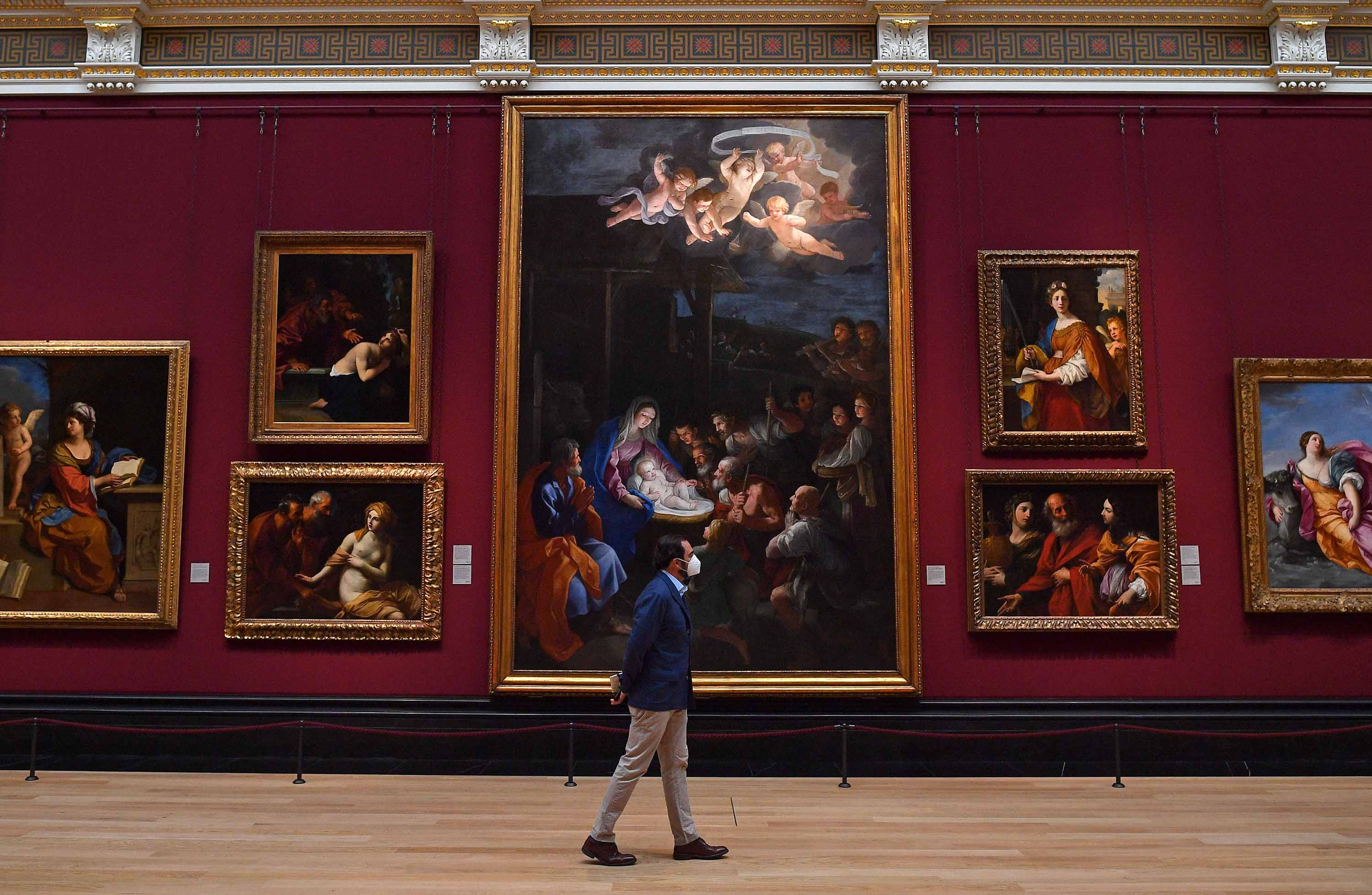 A member of staff wearing a protective face mask patrols a room inside the National Gallery in London on July 4, as the gallery prepares to reopen on July 8, following the easing of restrictions imposed during the novel coronavirus pandemic.