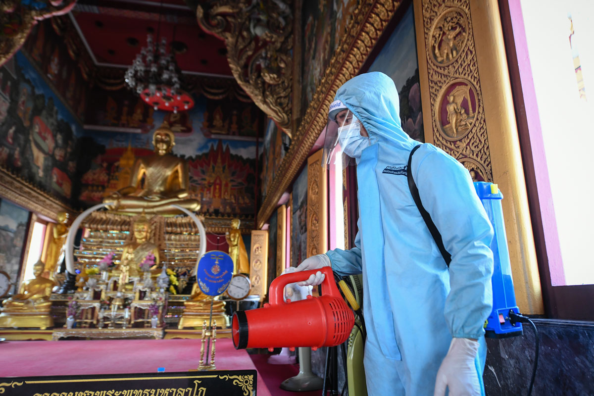 A rescue worker wearing personal protective equipment sprays disinfectant at Klong Toey Nok temple in Bangkok, Thailand on May 16.