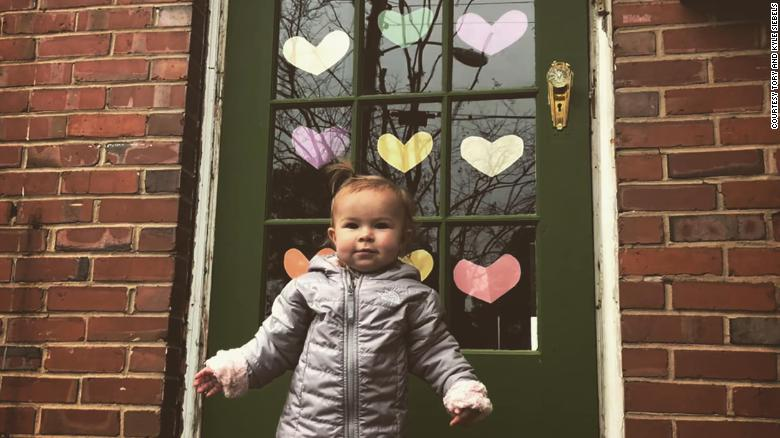 Nora Siebels stands outside her front door decked out in paper hearts in Norfolk, Virginia.
