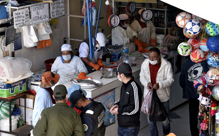 Workers and customers wear face masks as a preventive measure against the spread of the coronavirus at a market in La Paz on March 24.