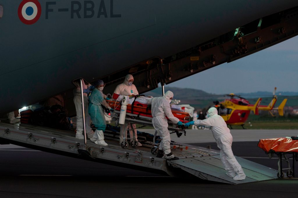 Medical staff carry a patient infected with the novel coronavirus at Aulnat airport, near Clermont-Ferrand, on April 3.