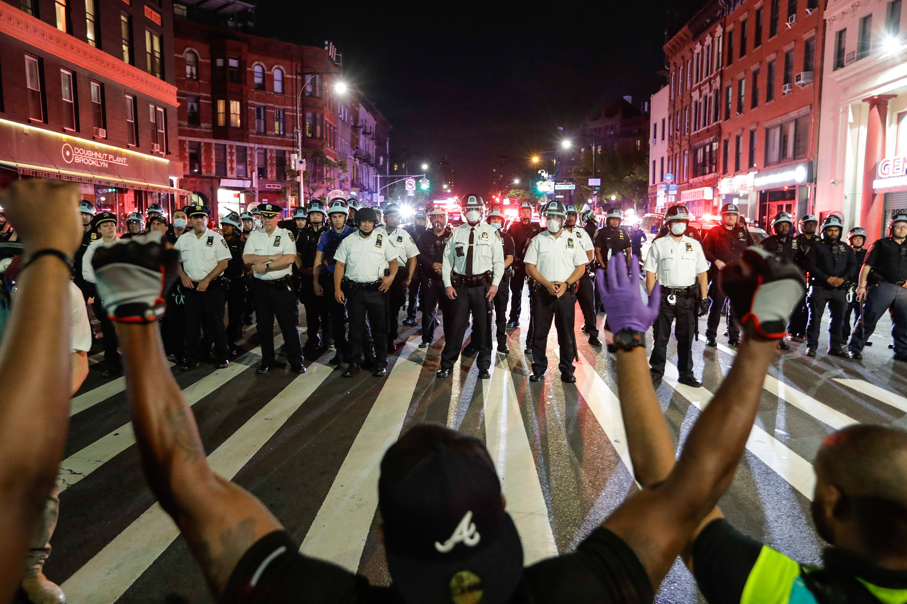 Protesters take a knee in front of police officers on June 4 in the Brooklyn borough of New York.