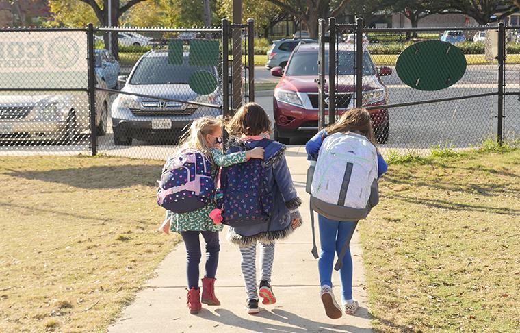 School children wearing facemasks walk outside Condit Elementary School in Bellaire,Texas, on December 16, 2020.