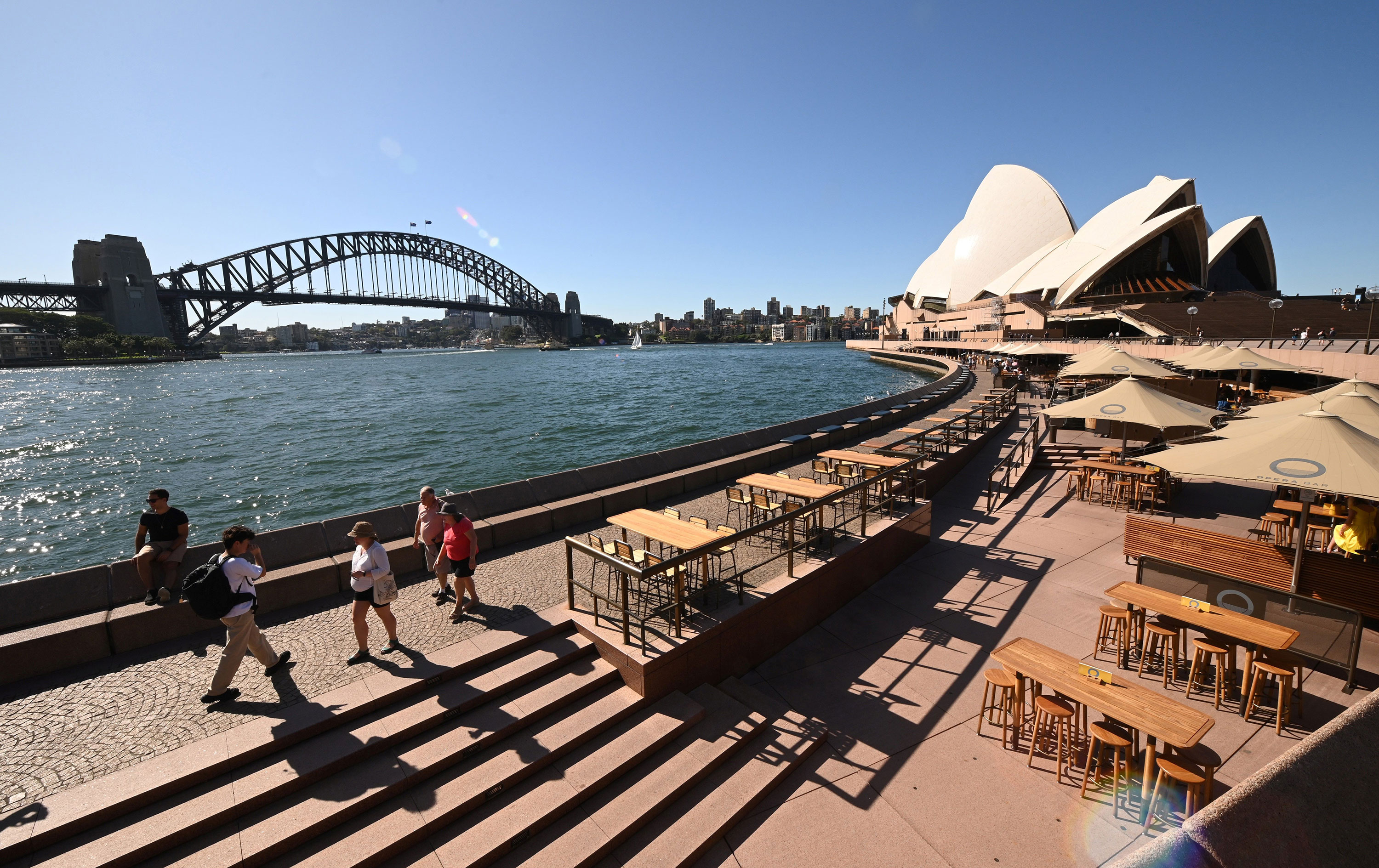 Tourists walk along Circular Quay in Sydney on March 20.