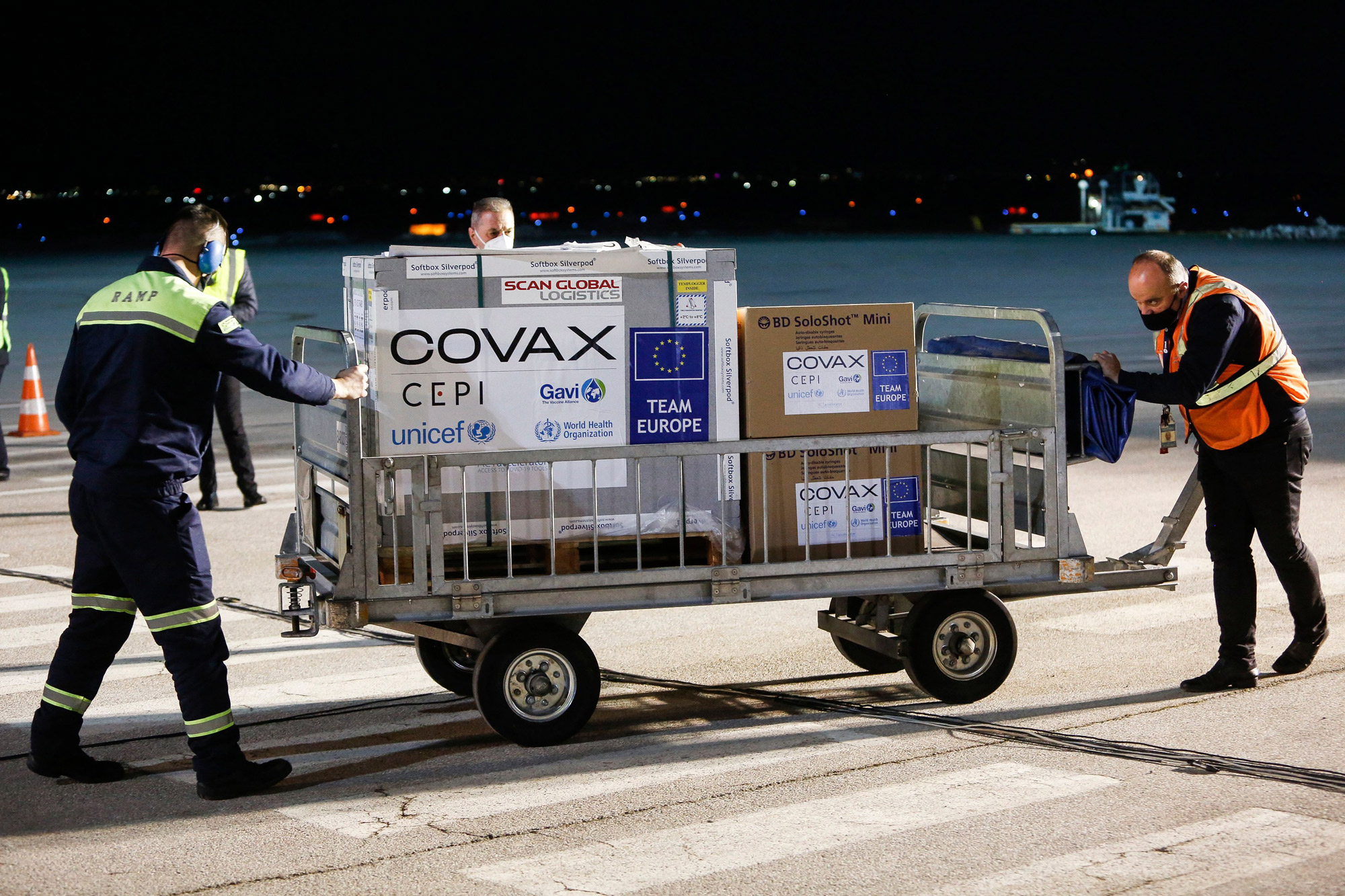 Airport employees push a cart carrying a shipment of AstraZeneca/Oxford Covid-19 vaccines at the Pristina International Airport on March 28.