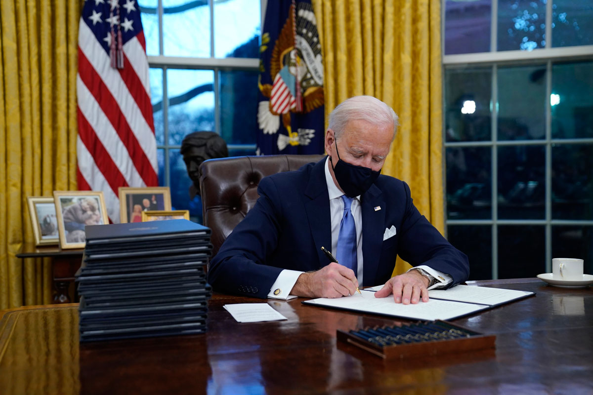 President Joe Biden signs his first executive order in the Oval Office of the White House on January 20.
