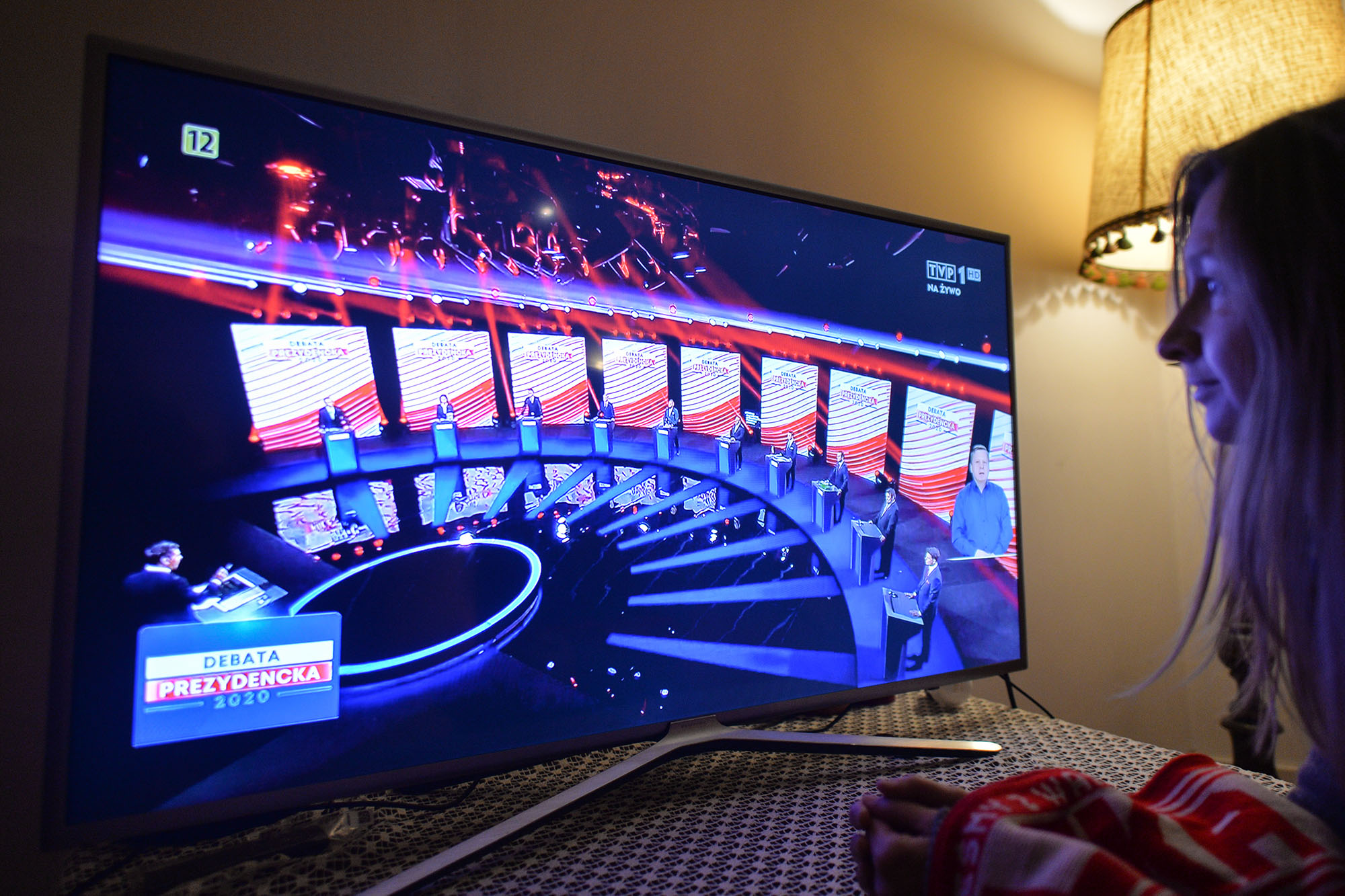 A woman watches the candidates take part in Poland's presidential debate in Krakow on May 6.