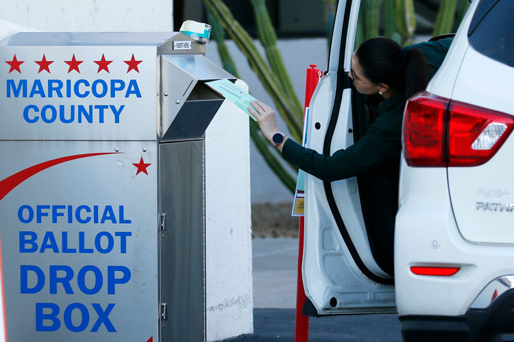 A voter drops off a ballot for the Arizona Democratic presidential preference election Tuesday, March 17, in Phoenix.