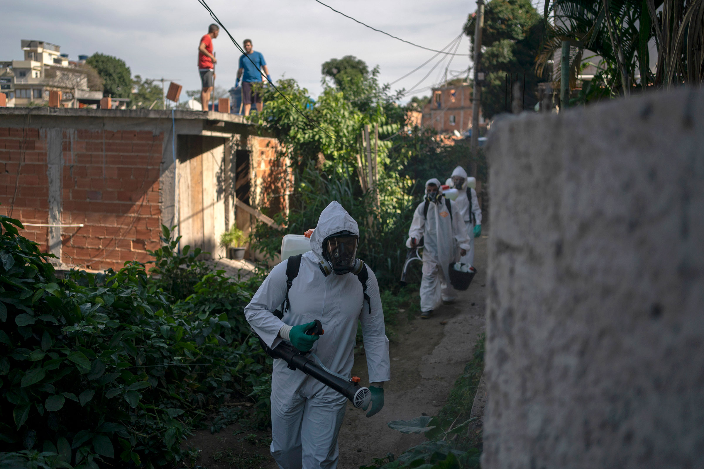 Volunteers spray disinfectant in a Rio de Janeiro alleyway to help contain the spread of the novel coronavirus on Sunday.