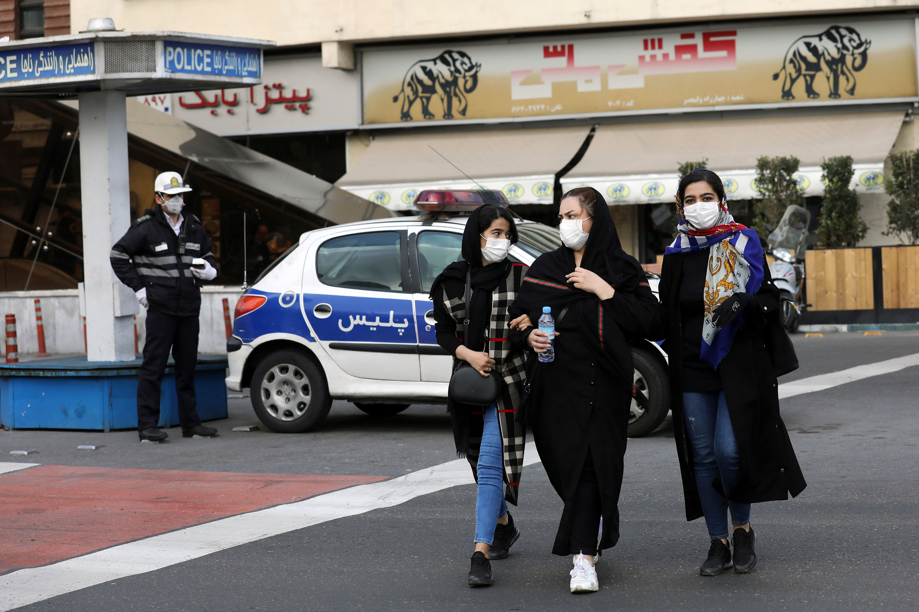 A policeman and pedestrians wear masks to help guard against the Coronavirus in downtown Tehran on February 23.