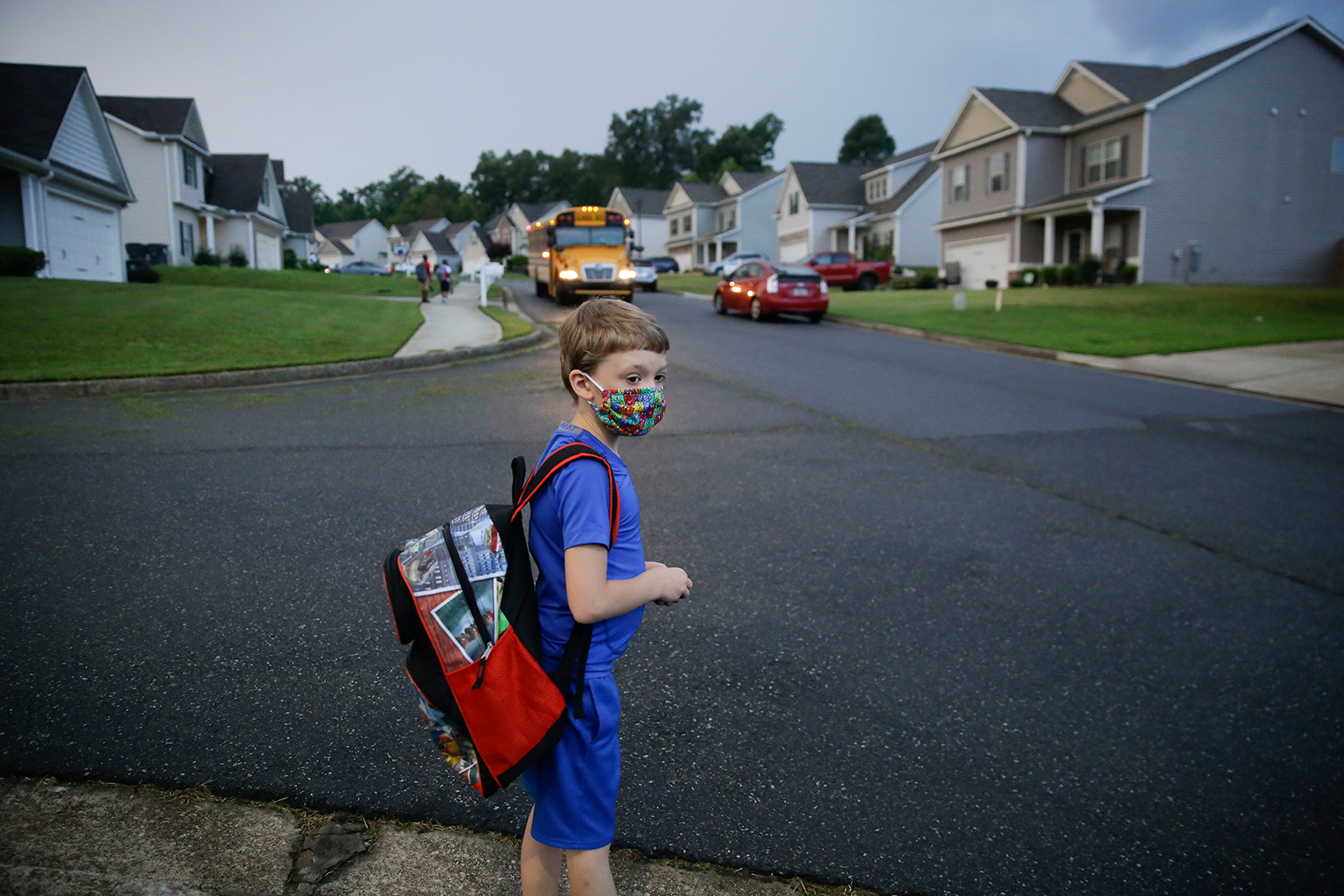Paul Adamus, 7, waits at the bus stop for the first day of school on Monday, Aug. 3, 2020, in Dallas, Georgia.