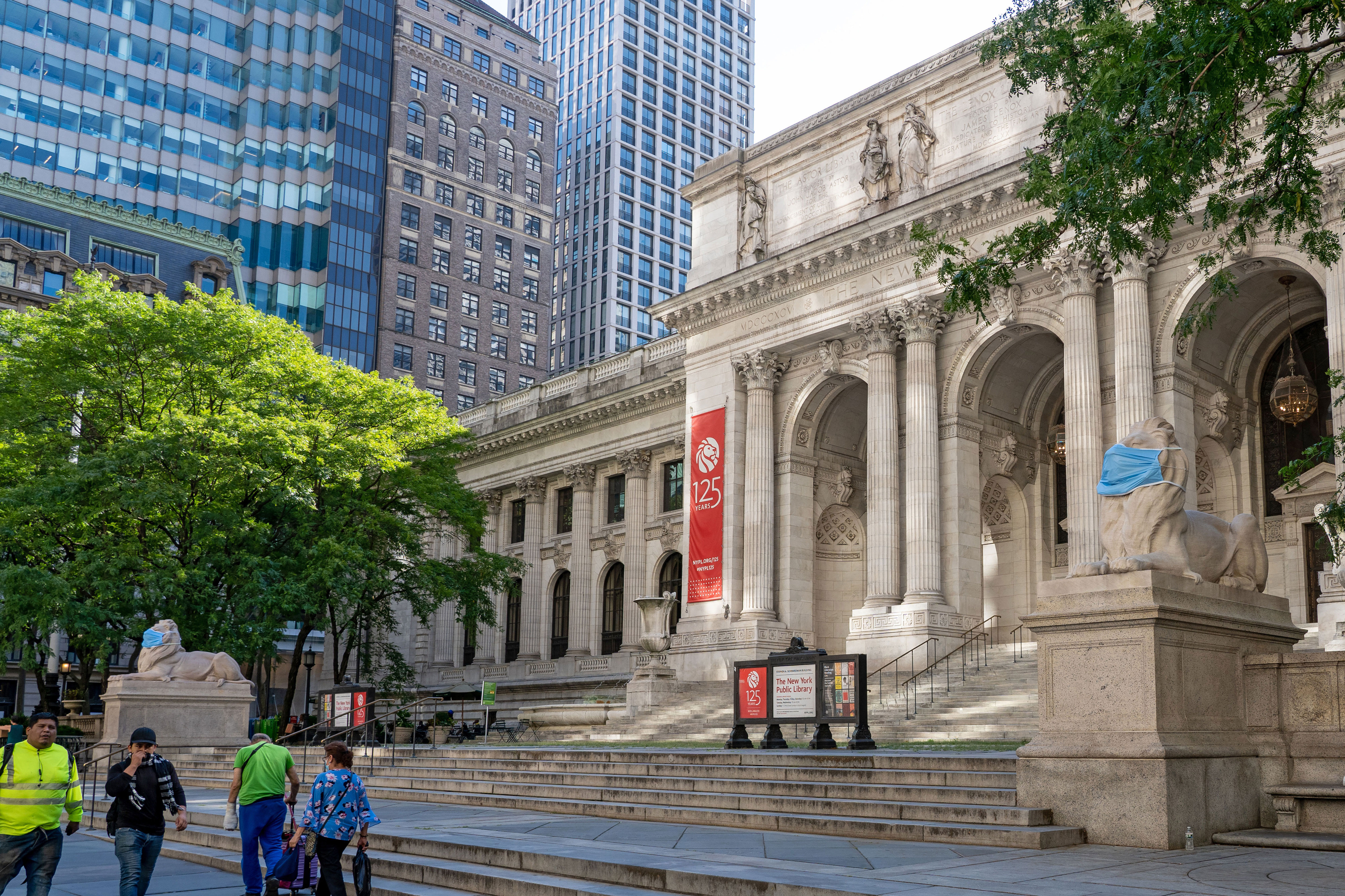 People walk by the New York Public Library in July 2020.