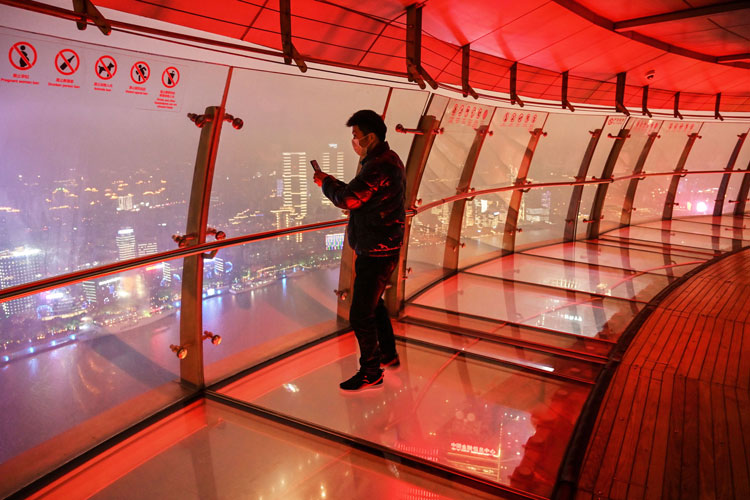 A man takes photos of Shanghai from the Oriental Pearl Tower Radio and Television Tower in Shanghai on March 12.