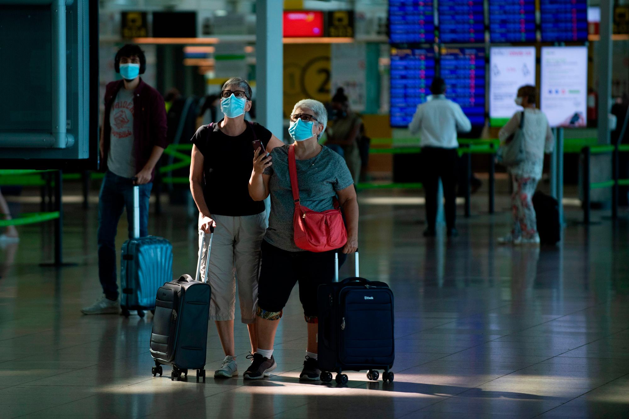 Passengers check their flight information on screens at the Josep Tarradellas Barcelona-El Prat airport in El Prat de Llobregat on July 6.