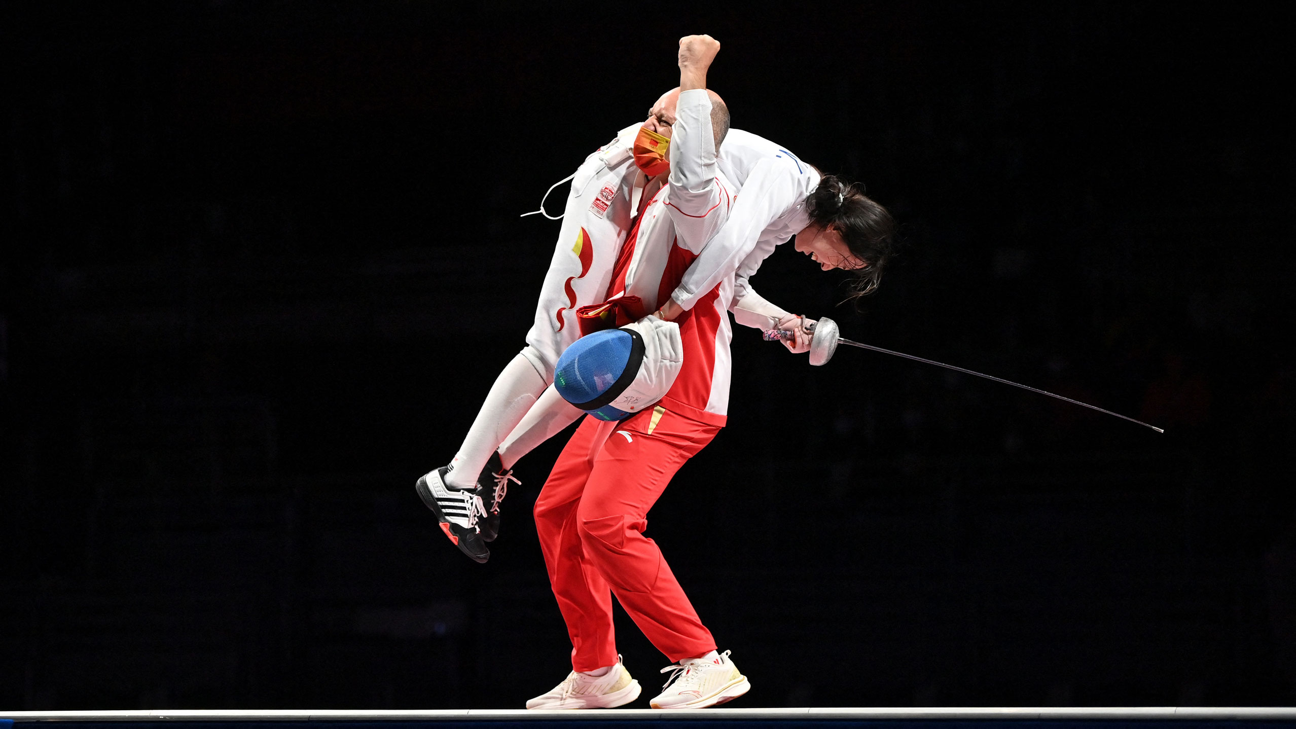 China's Sun Yiwen celebrates with her coach Hugues Obry after winning the gold medal in the women's epee individual bout on July 24.