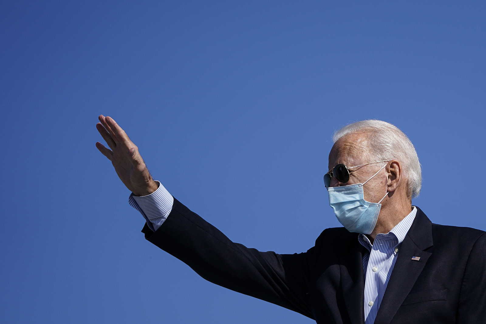 Democratic presidential nominee Joe Biden waves as he boards his campaign plane at New Castle Airport on October 22, in New Castle, Delaware.