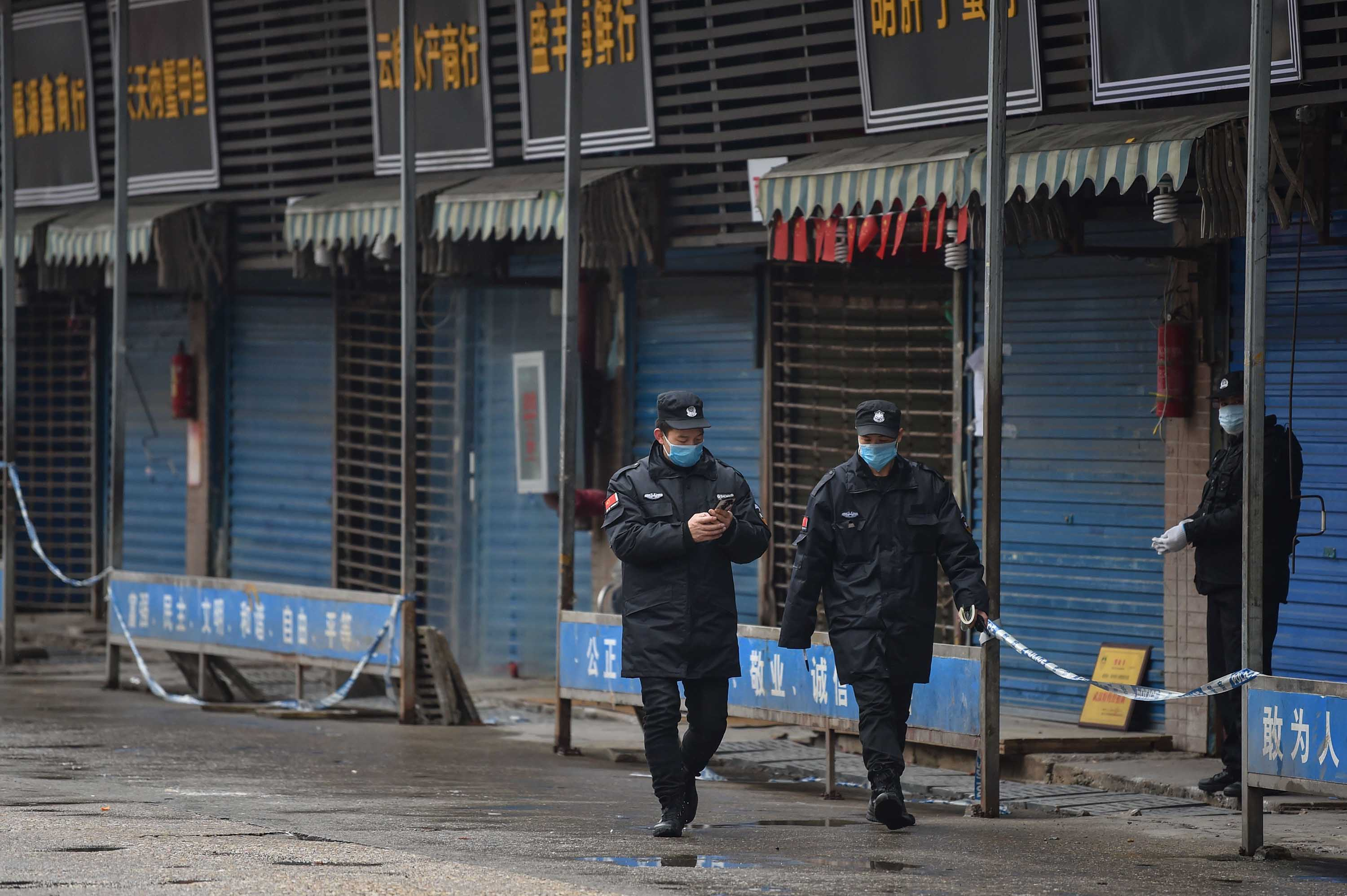 Guards patrol on January 24 outside the Huanan Seafood Wholesale Market in Wuhan, believed to be the source of the virus.