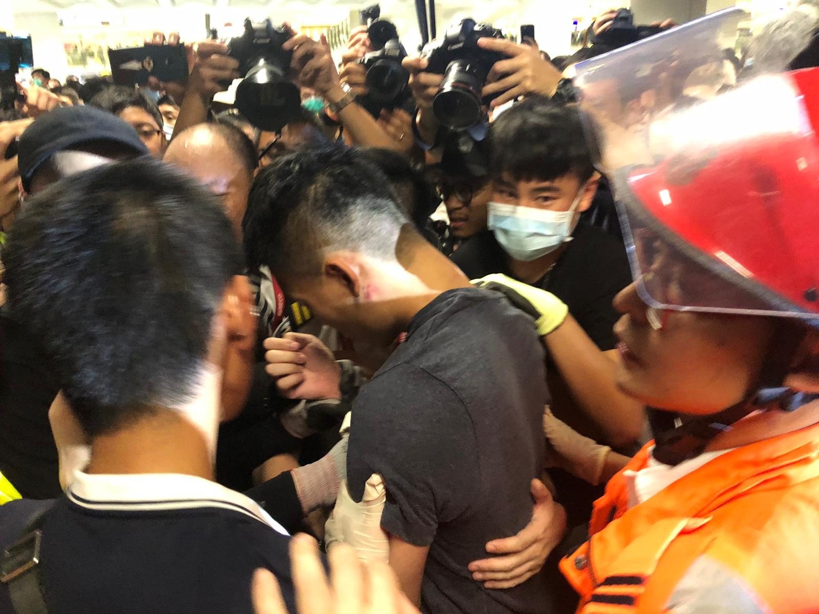 A man accused by protesters of being an undercover policeman has his hands zip-tied.