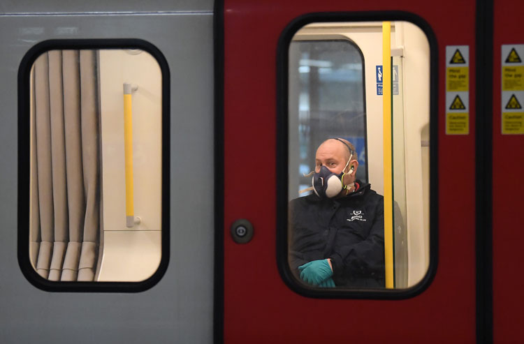 A member of the public wears a a protective mask on the Tube on March 25  in London, England.