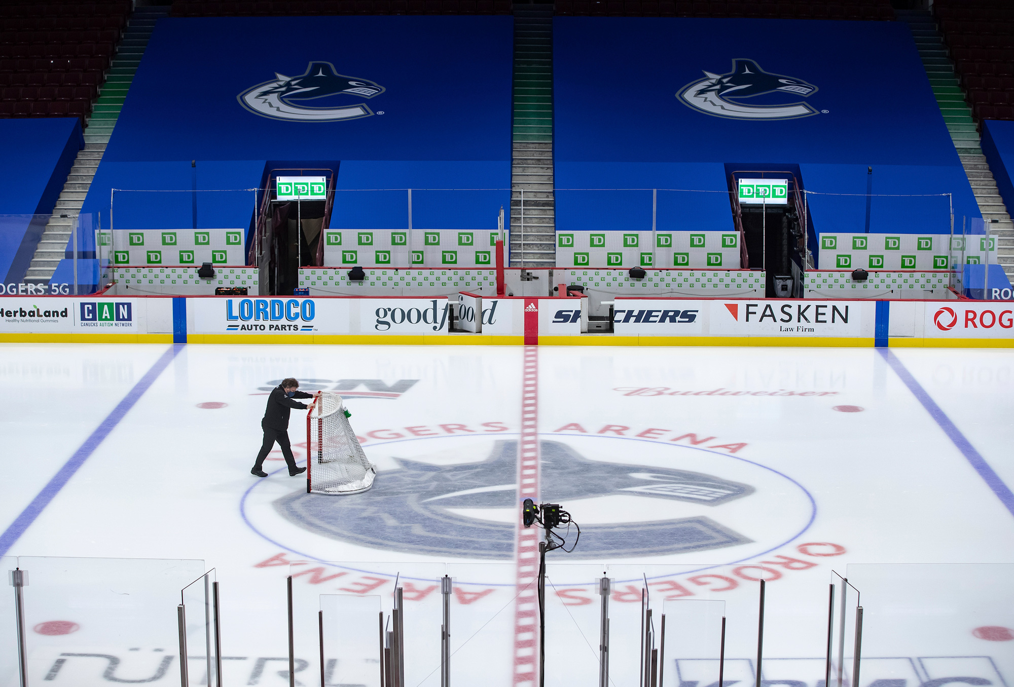 An arena worker removes the net from the ice after the Vancouver Canucks and Calgary Flames NHL hockey game was postponed due to a positive COVID-19 test result, in Vancouver, British Columbia, on March 31.