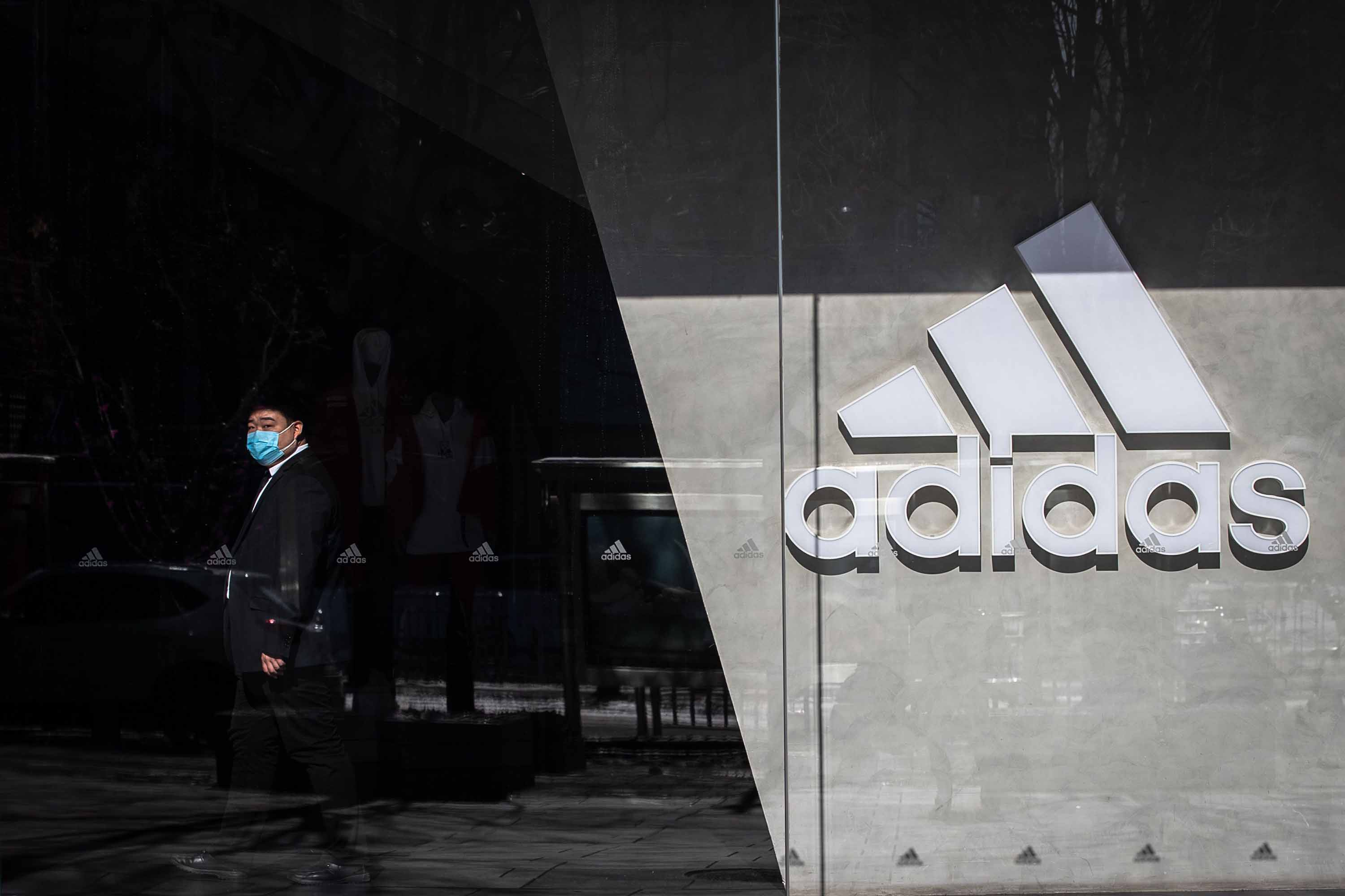 A security guard wearing a protective face mask stands on duty at an Adidas store in Beijing on February 8.