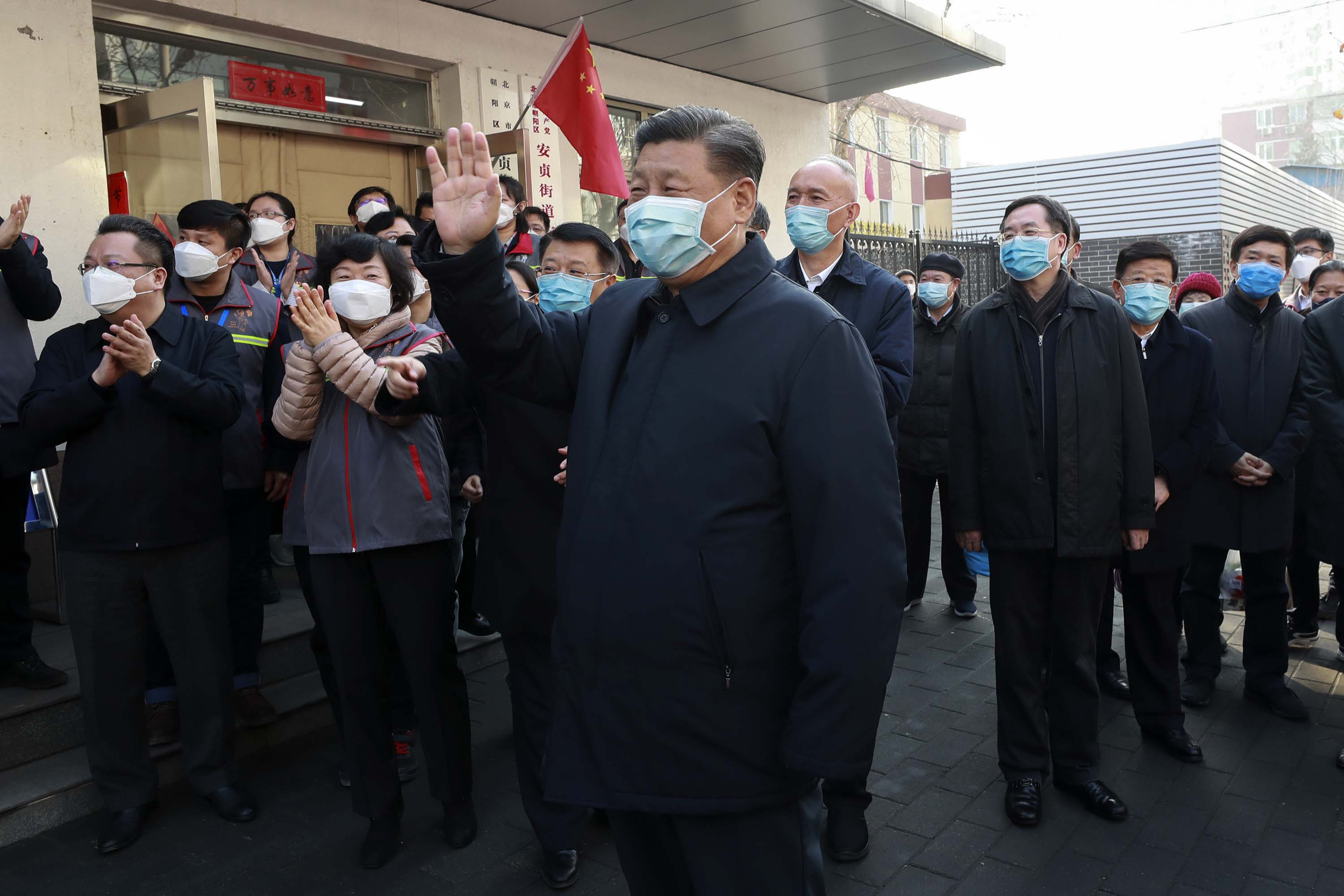 Chinese President Xi Jinping, center, wears a protective face mask during an appearance in Beijing on Monday.