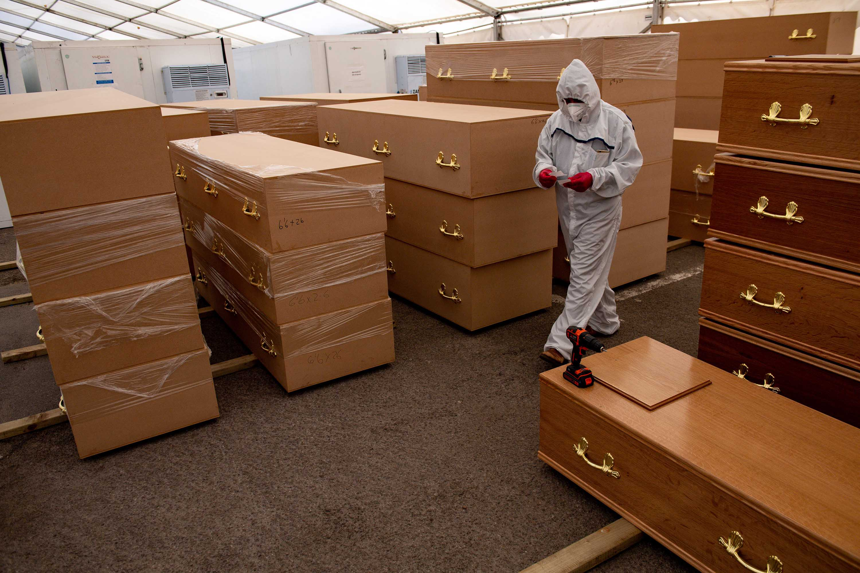 A volunteer walks past coffins in a temporary morgue for coronavirus victims at the Central Jamia Mosque Ghamkol Sharif in Birmingham, England, in April.