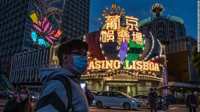 People wearing face masks walk in front of the Grand Lisboa Hotel on January 28 in Macao.