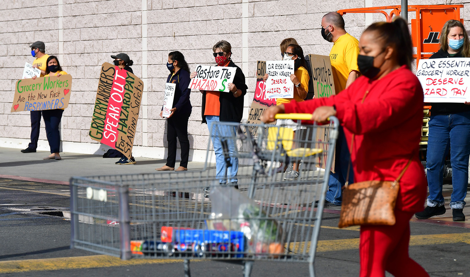 "Workers hold placards in protest at a Food 4 Less supermarket in Long Beach, California on February 3, after a decision by owner Kroger to close two stores rather than pay workers an additional $4 in ""hazard pay"" for their continued work during the pandemic."