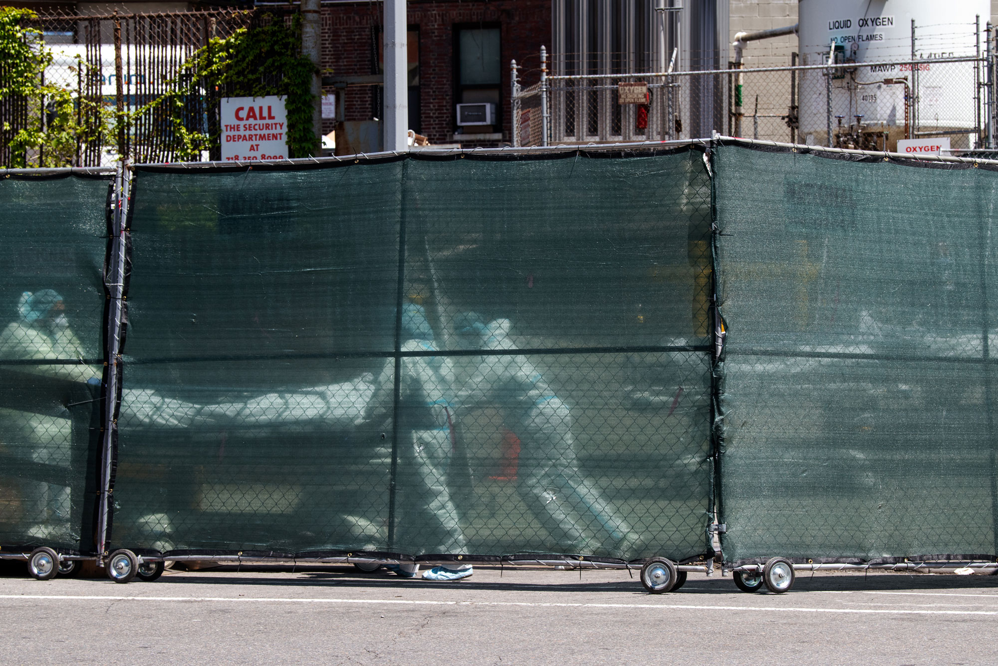 Hospital personnel behind a barricade move deceased individuals to the overflow morgue trailer outside The Brooklyn Hospital Center on May 7, in the Brooklyn borough of New York City.