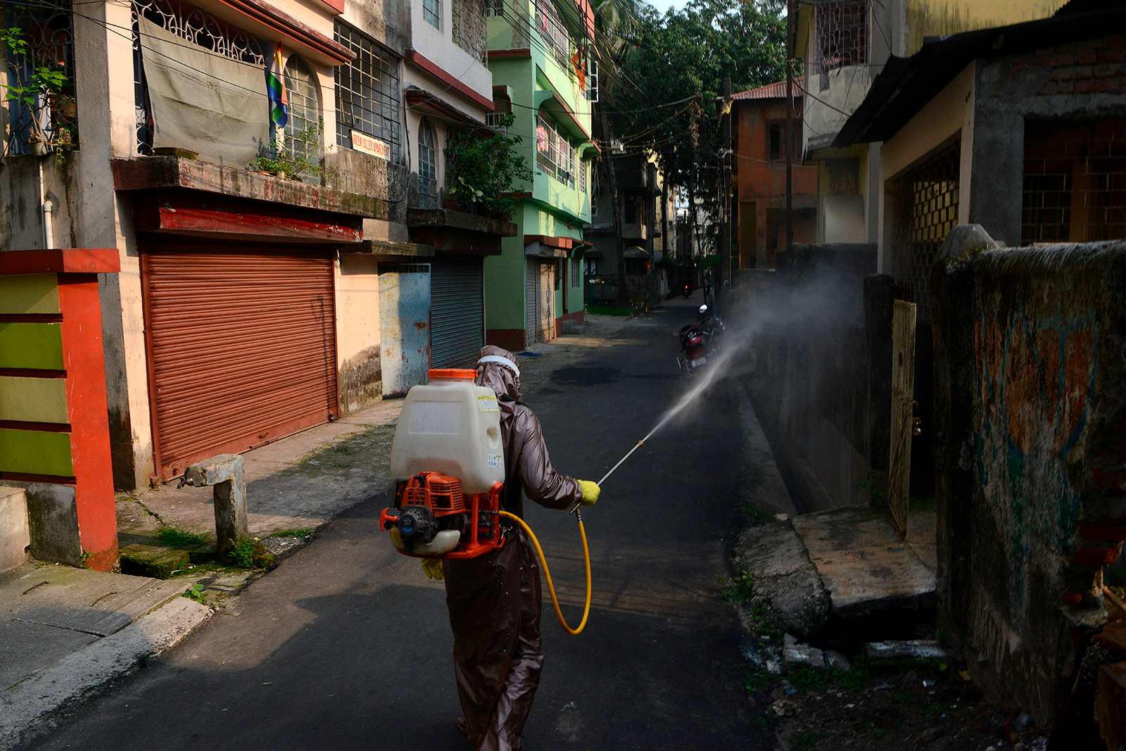 A municipal worker sprays disinfectant in an alley where a patient had tested positive for the coronavirus in Siliguri, India on May 18.