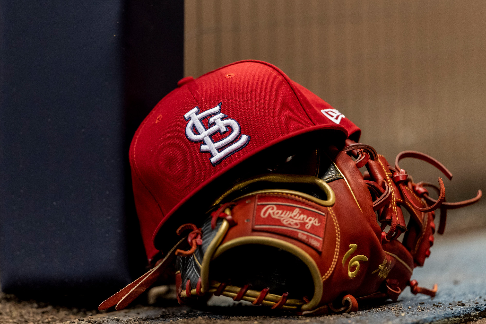 A St. Louis Cardinals hat and glove sit on the dugout step during a MLB game at Miller Park in Milwaukee, Wisconsin, on March 29, 2019.